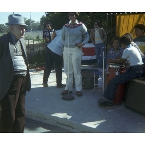 Woman speaks into microphone at a Latino street festival, while onlookers listen and musicians wait to play music.