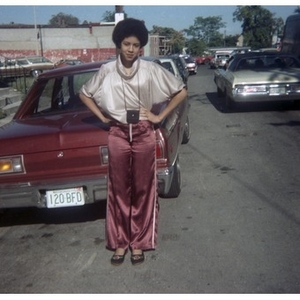 Full-length portrait of a Hispanic American woman, facing front, wearing athletic pants, standing in front of a red car that is parked in the street at a Latino street festival.