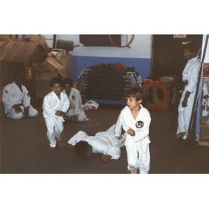 Three Latino boys performing a karate demonstration (one boy has fallen to the floor), while three older karate mentors watch, in a classroom at the Festival Betances, Boston, 1986.