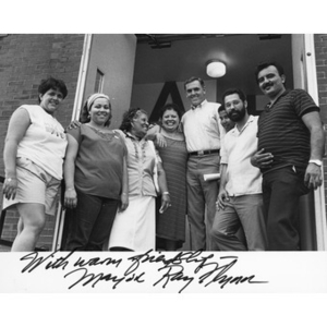 Mayor Ray Flynn (standing fifth from left) outside a brick building, with a group of four women and three Latino men, at a political event.
