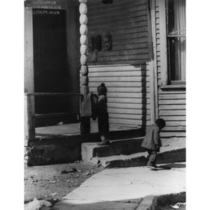 Two African American children play outside of a dilapidated house on Oakborn Avenue, Roxbury, Mass.