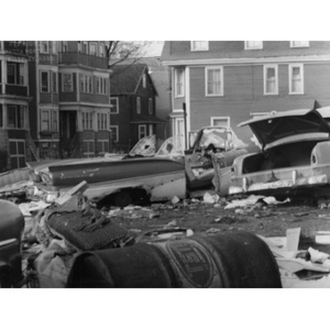Abandoned cars, trash, and debris in a lot in front of residential buildings in Roxbury, Mass.