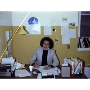 Male employee with Afro haircut, seated behind a desk, writing, at La Alianza Hispana offices, Roxbury, Mass.