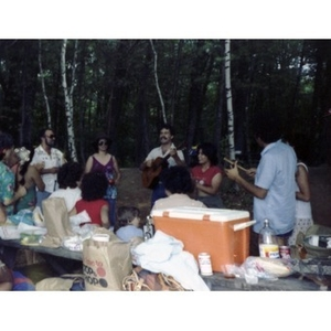 Approximately fourteen people play musical instruments, sing, and clap their hands by a table covered with food, at a La Alianza staff picnic at an unidentified location in the woods.
