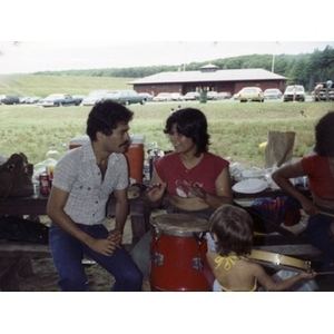 Smiling woman is seated at a picnic table playing the drums at a La Alianza staff picnic, while a man sits next to her.