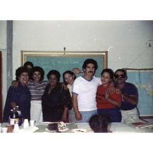 Group photo of five female and three male staff workers at a party at La Alianza Hispana, Boston.