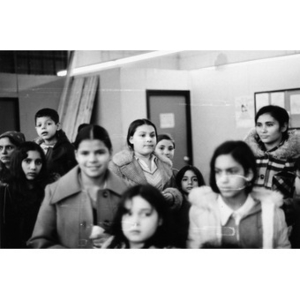 Group of eight girls, one boy, and one woman watch a Three Kings' Day pageant at La Alianza Hispana.