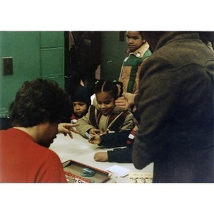 Four children stand in front of a table to receive a numbered [raffle?] ticket and are helped by two adults at the Three Kings' Day celebration at La Alianza Hispana, Roxbury, Mass.