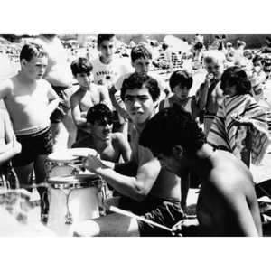 Group of Latino children listen to two youths playing the drums at the beach, at an outing sponsored by La Alianza Hispana.
