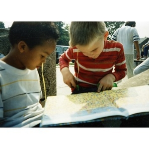 Two young boys look at a picture book, seated outside.