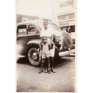 Belle and a young girl stand in front of a car.