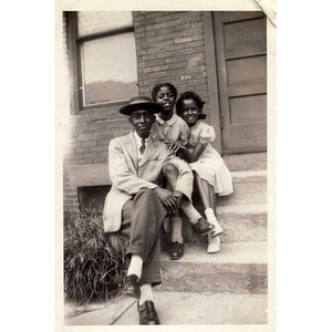 A young Reverend Michael E. Haynes poses with two unidentified girls.