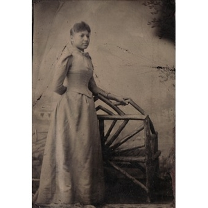 An African-American woman standing by a wooden bench.