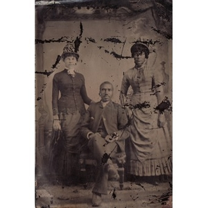 Two African-American women standing next to a seated African-American man.