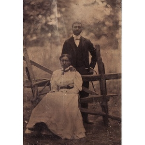 An African-American couple posing by a fence.