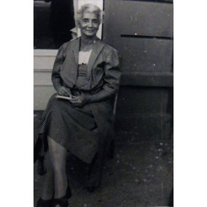 An African-American woman sitting outside of a house.