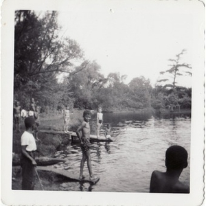 A group of boys stand at the edge of a manmade lake at Breezy Meadows Camp.