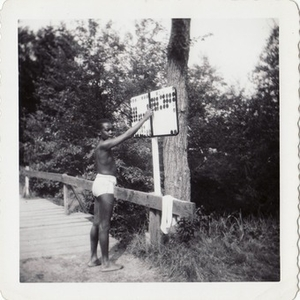 A boy in swimming trunks poses in front of a sign at Breezy Meadows Camp.
