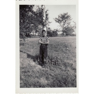 Boy leans against a totem pole in a field at Breezy Meadows Camp.