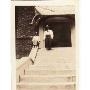 Two men pose on steps under a banner