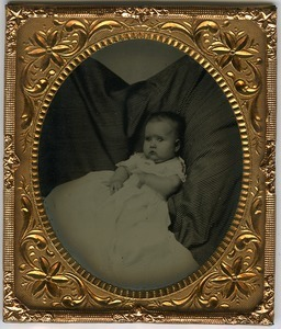 Portrait of unidentified infant in ample gown, lying on a striped pillow
