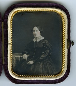 Emily A. Scott Cleveland: three-quarter length studio portrait seated at a table, in velvet covered case