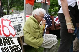 Older woman seated during an anti-Iraq War protest