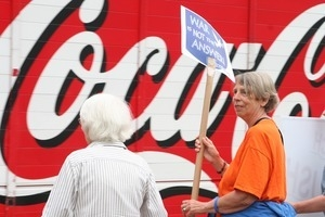 Anti-Iraq War protester with sign reading 'War is not the answer,' with huge Coca Cola sign in the background