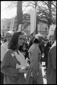 Woman holding a cutout cardboard peace dove and antiwar demonstrators standing in front of the White House during the March on Washington