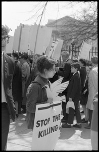 Woman holding a cutout cardboard peace dove and a sign reading 'Stop the killing', marching with antiwar demonstrators standing in front of the White House during the March on Washington