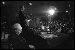Arthur M. Schlesinger, Jr., speaking at the National Teach-in on the Vietnam War, with other seated panelists Hans J. Morgenthau (left) and Isaac Deutscher