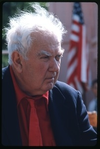 Alexander Calder: three-quarter profile bust portrait in a red tie, with an American flag in the background