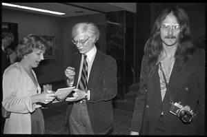 Andy Warhol mingling at a reception at the Birmingham Museum of Art, another photographer at right