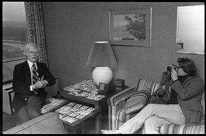 Andy Warhol being photographed while seated with an array of polaroids at the Birmingham Museum of Art