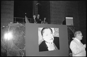 Andy Warhol standing on a platform above his unveiled portrait of Charles Ireland, during a reception at the Birmingham Museum of Art