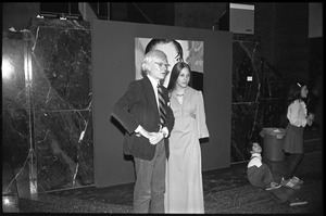 Andy Warhol and unidentified woman standing in front of his unveiled portrait of Charles Ireland at a reception at the Birmingham Museum of Art