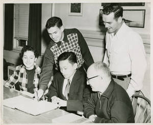 Group of people looking an open Notebook