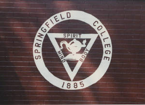 Springfield College seal painted on a brick wall, ca. 1990