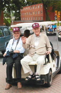 Two members of the Class of 1952 on back of golf cart