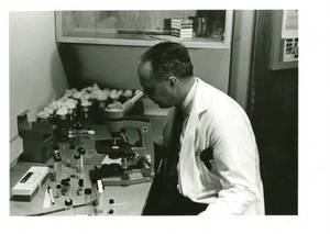 Dr. Harry M. Smith looking through a microscope