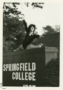 Joanne Egan doing the splits on the main Springfield College campus sign