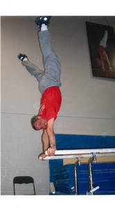 Stephen E. Posner performing handstand on parallel bars, 1999