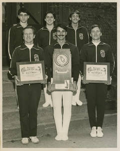 Springfield College Gymnasts and coach Wolcott with awards for 1976-1977 season, including NCAA Division II Championship Trophy
