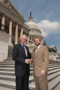 Congressman John W. Olver (center) shaking hands with unidentified man, posed on the steps of the United States Capitol building