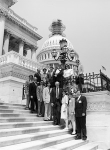 Congressman John W. Olver (4th from right) and visitors, posed on the steps of the United States Capitol building (scaffolding on top of dome)