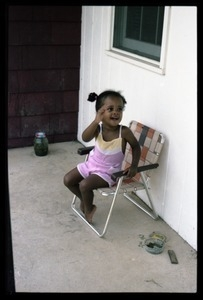 Zena Allen seated in a folding chair on a porch