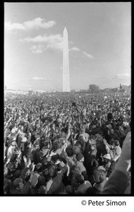 Massive crowd raising hands in peace symbols, with Washington Monument in background: Vietnam Moratorium march on Washington