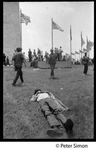 Man lying on the grass near the Washington Monument, with protesters assembling in the background during the March on the Pentagon (mobilization on Washington)