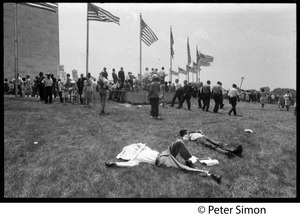 Men lying on the grass near the Washington Monument, with protesters assembling in the background during the March on the Pentagon (mobilization on Washington)