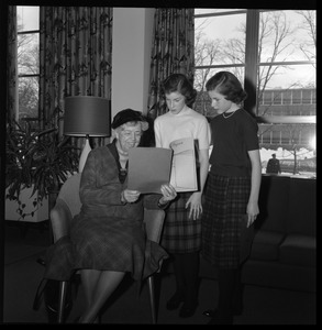 Eleanor Roosevelt (center) seated in the Cape Cod Lounge (Student Union), reading a book report presented by two young girls, during Roosevelt's Distinguished Visitors Program appearance at UMass Amherst